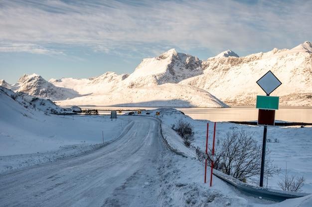 Neige sur route de campagne avec panneau de signalisation dans la vallée