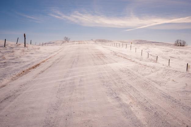 Neige soufflant sur une route de gravier dans un hiver de la saskatchewan