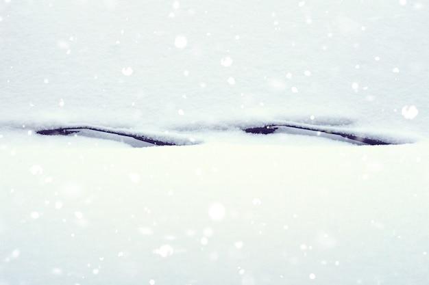 La neige sur la voiture se bouchent. pare-brise et capot dans la neige