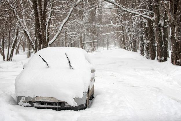 Neige sur les voitures dans le parc après les chutes de neige. scène urbaine d'hiver