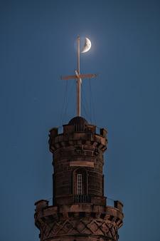 Le nelson monument sur calton hill la nuit devant le croissant de lune edimbourg en ecosse