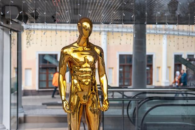 Nequin doré debout dans une vitrine. vente de choses et concept de vente.