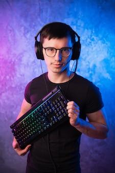 Nerd informatique avec clavier sur mur éclairé au néon rose et bleu coloré