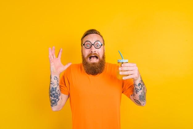 Nerd peur homme avec des lunettes boit un jus de fruits