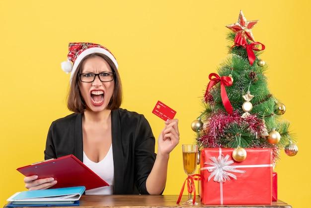 Nerveuse charmante dame en costume avec chapeau de père noël et lunettes montrant la carte bancaire au bureau