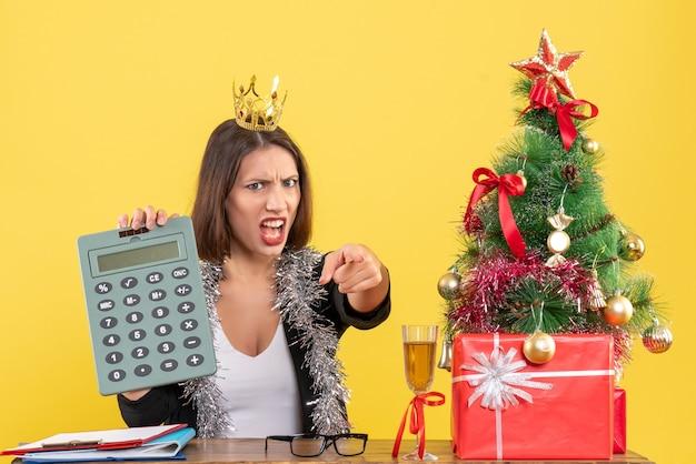 Nerveuse charmante dame en costume avec couronne tenant calculatrice au bureau