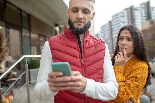 Nerveuse jeune femme debout derrière son petit ami tout en voulant voir ses messages