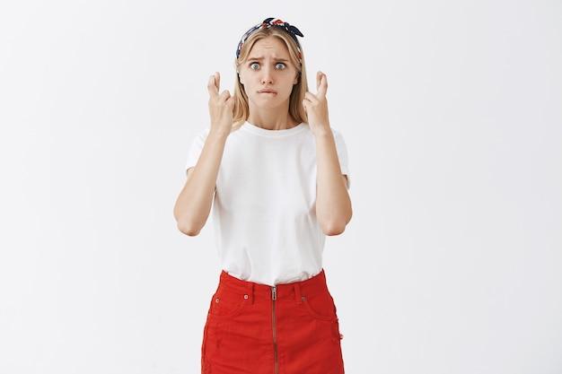 Nerveuse jeune fille blonde posant contre le mur blanc