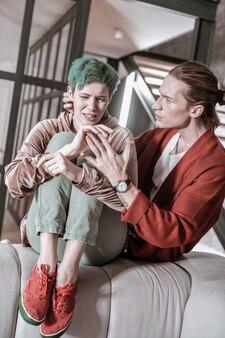 Nerveux après le combat. petite amie aux cheveux verts portant des baskets rouges se sentant nerveuse après une bagarre avec son homme