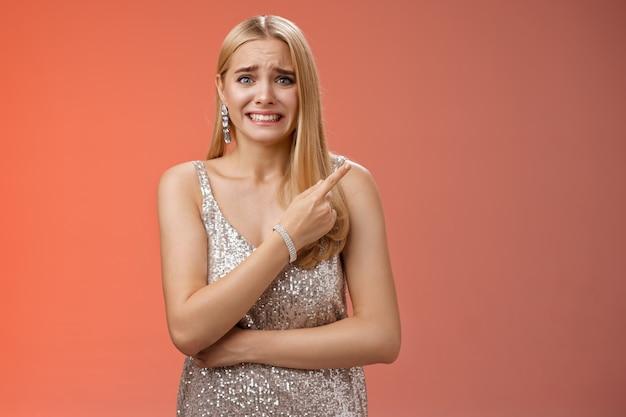 Nerveux hésitant jolie femme blonde inquiète grinçant des sourcils froncement serrer les dents pointant derrière chercher des amis aider à voir ex-petit ami ne veut pas être vu, debout anxieux fond rouge de partie maladroite.