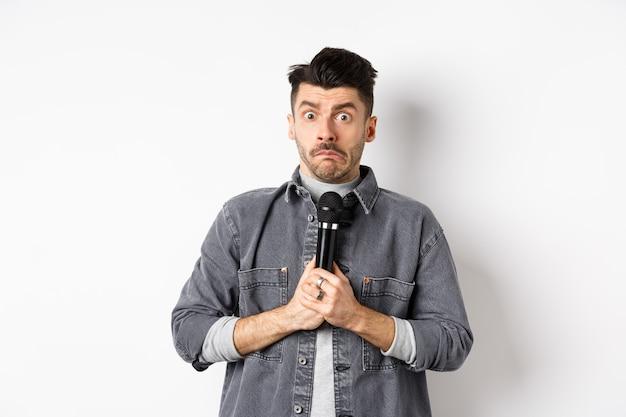 Nerveux mec non confiant tenant le microphone et l'air indécis, peur d'effectuer, debout timide sur fond blanc.