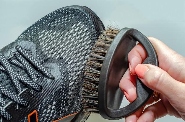 Nettoie les chaussures de sport, la femme nettoie les chaussures avec une brosse. nettoyer des chaussures de course sales