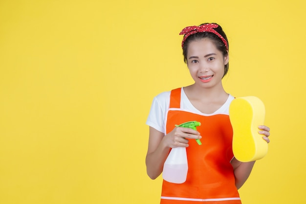Nettoyage . une belle femme avec un appareil de nettoyage sur un jaune.