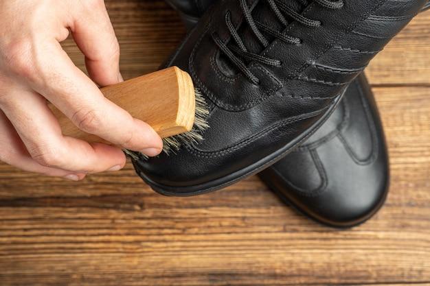 Nettoyage des bottes en cuir noir de polissage avec une brosse et du cirage pour chaussures