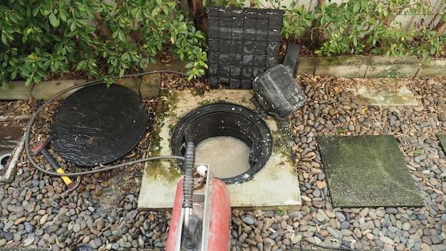 Nettoyage des canalisations. plombier réparant le bac à graisse bouché avec la machine à vis. entretien du système d'égout et du bac à graisse par un plombier professionnel. utiliser un serpent à vis pour réparer et déboucher un drain.