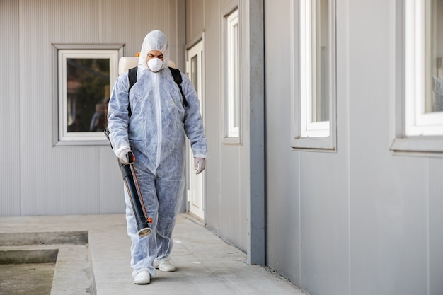 Nettoyage et désinfection à l'extérieur autour de la combinaison et du masque du bâtiment.