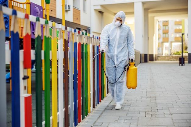 Nettoyage et désinfection à l'extérieur autour de la maternelle, l'épidémie de covid-19. équipes de session pour les efforts de désinfection. prévention des infections et contrôle de l'épidémie. costume et masque.