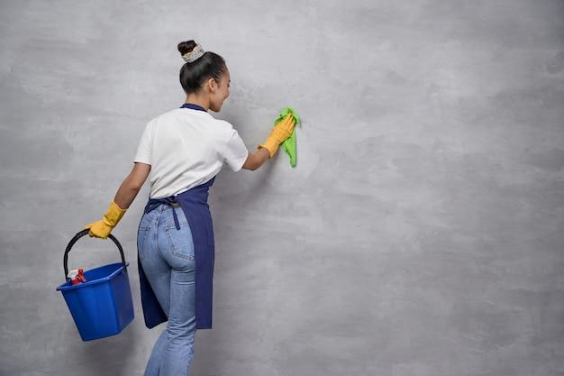 Nettoyage et désinfection de la maison. vue arrière de l'uniforme de la femme au foyer ou de la femme de chambre et des gants en caoutchouc jaune tenant un seau ou un panier avec différents produits de nettoyage et nettoyant un mur