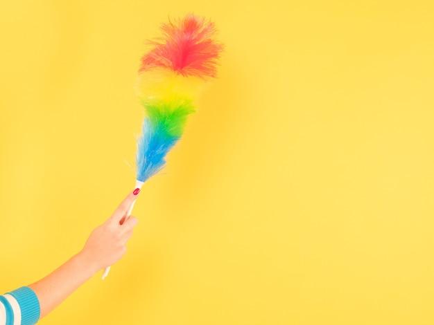Nettoyage à domicile de qualité. main de femme avec plumeau coloré. copiez l'espace sur fond jaune.