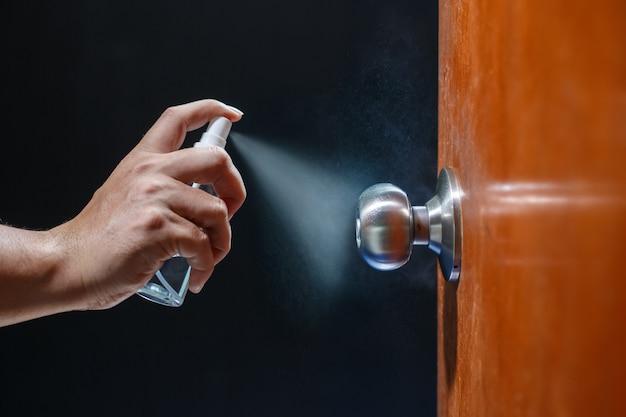 Nettoyage du bouton de porte avec un spray d'alcool pour la prévention de covid-19 (coronavirus)