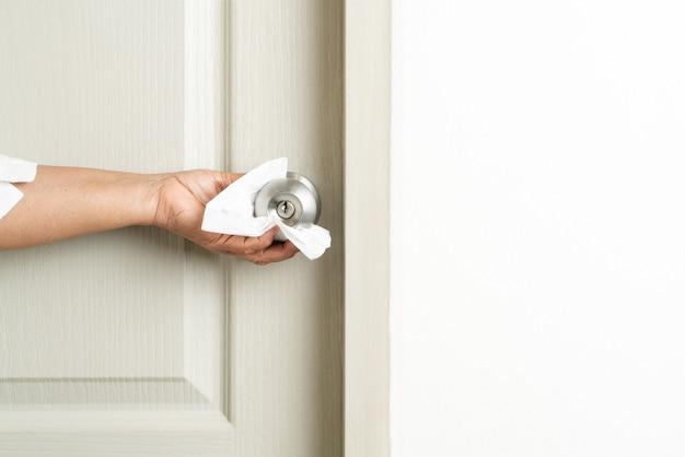 Nettoyage du bouton de porte avec un spray d'alcool pour la prévention du coronavirus covid-19