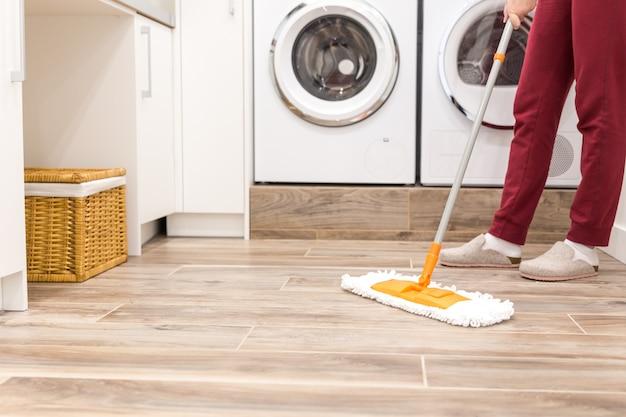 Nettoyage du sol dans la buanderie de la maison moderne