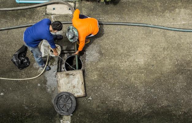 Nettoyage du tuyau de drainage par deux travailleurs pour se débarrasser de l'obstruction