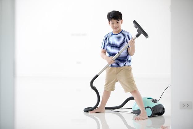 Nettoyage de l'enfant asiatique heureux dans la maison