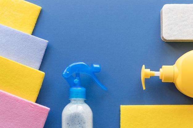 Nettoyage et entretien ménager, fond bleu. détergents pour nettoyer ou désinfecter la pièce. bouteilles, chiffon, désinfection maison. spray nettoyant, éponge pour le nettoyage avec espace copie, vue de dessus.