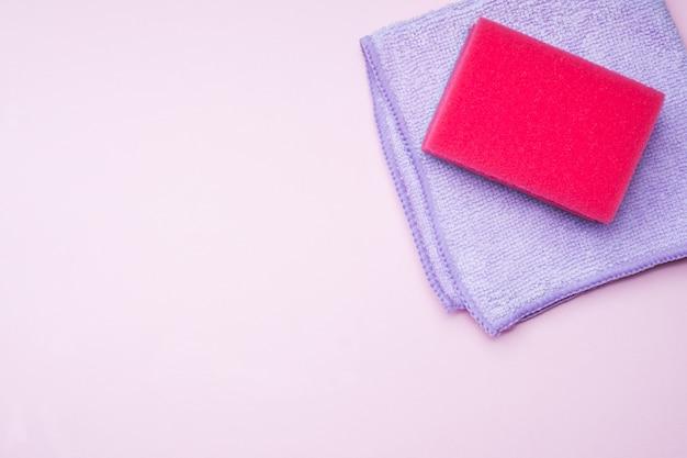 Nettoyage des éponges et des pinceaux de couleurs sur fond rose.