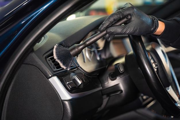 Nettoyage des évents de voiture avec une brosse.