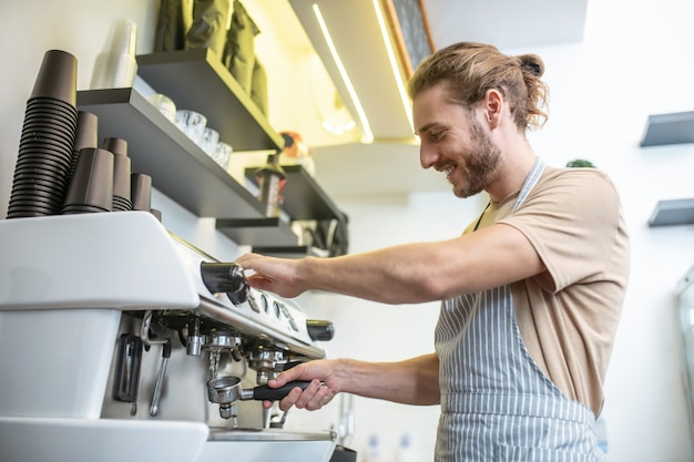 Nettoyage de filtre, cafetière. jeune adulte souriant homme bien informé en tablier de nettoyage filtre machine à café dans le café