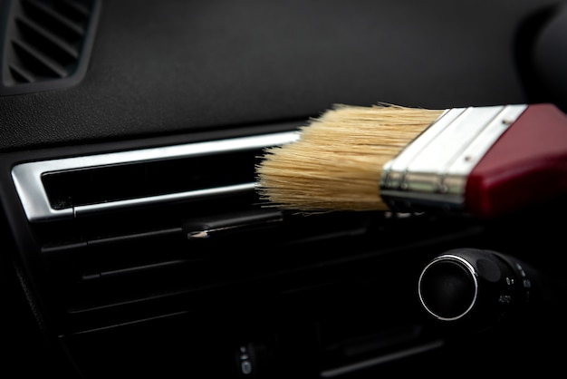 Nettoyage de la grille d'aération du climatiseur automobile avec une brosse.