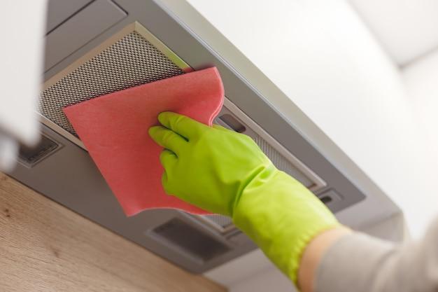 Nettoyage de la grille de la hotte domestique avec une serviette en fibre de tissu rose.
