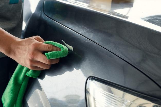 Nettoyage homme sur capot voiture avec chiffon en microfibre et décapant nettoyant