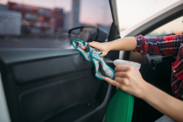 Nettoyage humide de l'intérieur de la voiture sur lave-auto. dame sur lavage automobile en libre-service. nettoyage de véhicules extérieurs le jour d'été