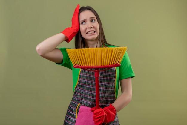 Nettoyage insatisfait jeune fille en uniforme en gants rouges tenant une vadrouille mettre sa main sur la tête sur un mur vert