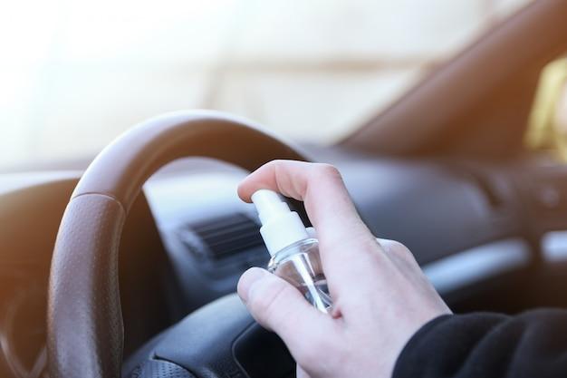 Nettoyage de l'intérieur de la voiture et pulvérisation de liquide de désinfection. désinfection du volant et des poignées de la voiture. coronavirus, covid-19 protection.désinfection du véhicule à l'intérieur,