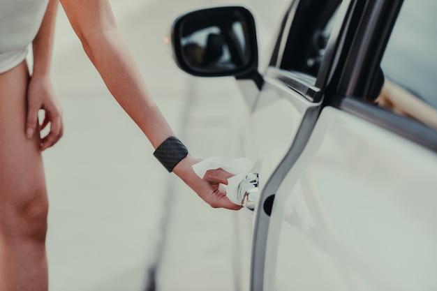 Nettoyage à la main d'une femme sur la poignée de porte de voiture, à l'extérieur de la voiture contre le nouveau coronavirus ou la maladie à virus corona (covid-19). concept antiseptique, hygiène et santé