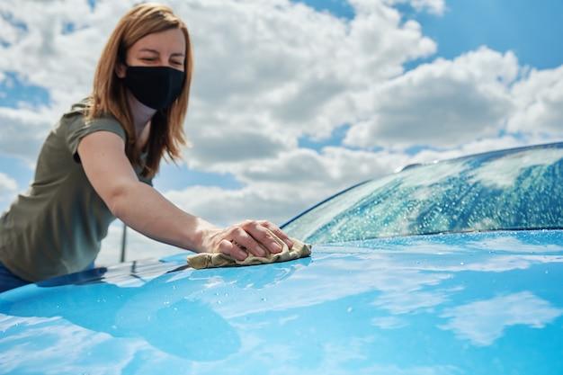 Nettoyage à la main d'une voiture bleue moderne avec un chiffon en microfibre