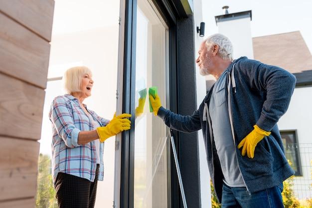Nettoyage avec mari. belle dame âgée se sentant positive lors du nettoyage des portes avec son mari