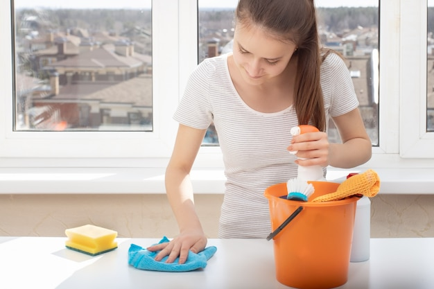 Nettoyage de meubles, tapis, revêtements de sol. jeune fille avec des produits de nettoyage pour la salle de bain, lavabo, toilettes, éponge et chiffons