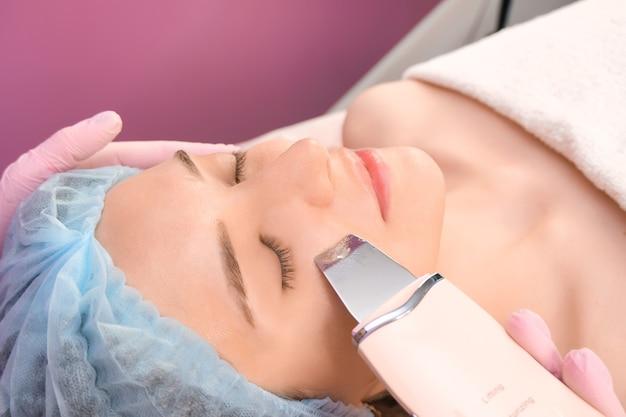Nettoyage par ultrasons du visage d'une jeune femme dans un cabinet de cosmétologie.