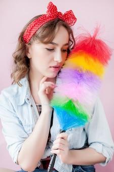 Nettoyage pin up femme. sourire pin-up tient une brosse à plumeau colorée