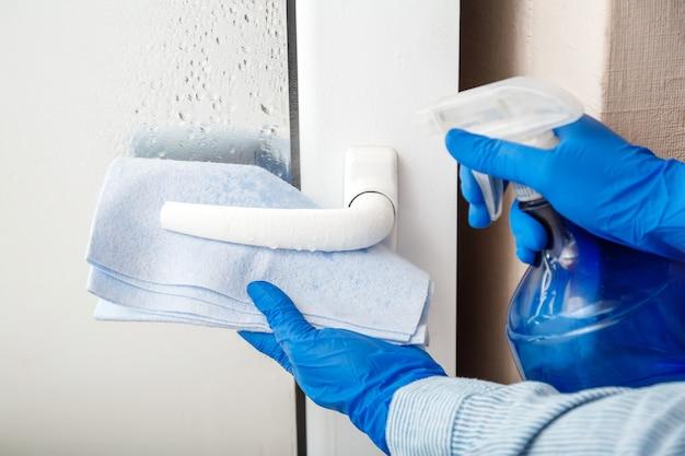 Nettoyage de la poignée de porte par pulvérisation d'alcool antibactérien femme de ménage dans des gants bleus en caoutchouc nettoyer le bouton de porte par un chiffon en tissu nouveau coronavirus covid normal dans la désinfection des surfaces