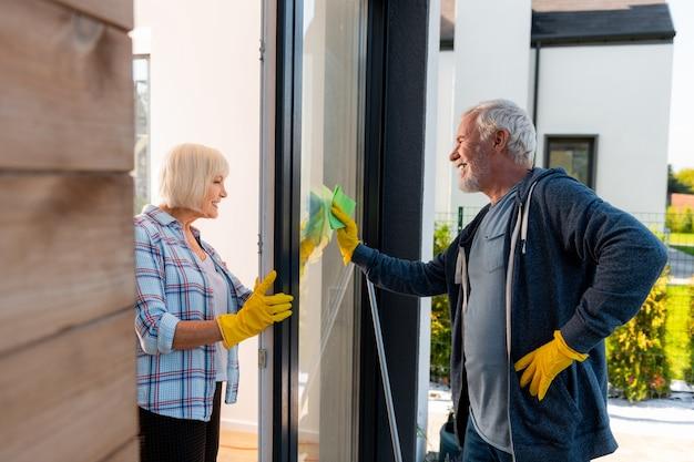 Nettoyage des portes. mari et femme âgés émotionnels positifs nettoyant les portes de la maison d'été ensemble