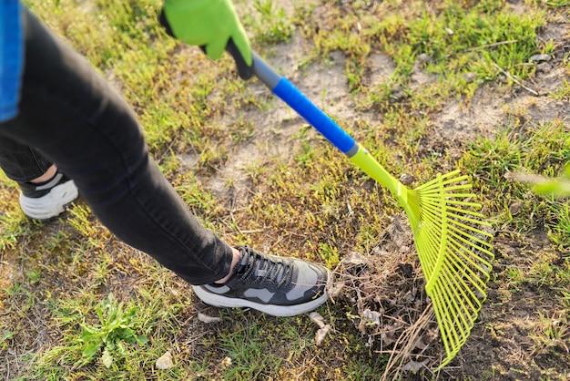 Nettoyage de printemps dans le jardin, râteau en gros plan nettoyant l'herbe verte de l'herbe sèche et des feuilles
