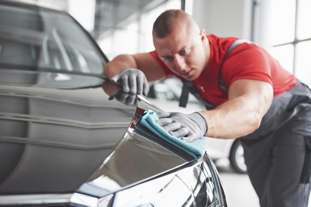 Nettoyage professionnel et lavage de voiture dans la salle d'exposition automobile.