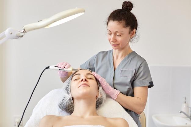 Nettoyage ultrasonique du visage. la jeune fille a une desquamation échographique.