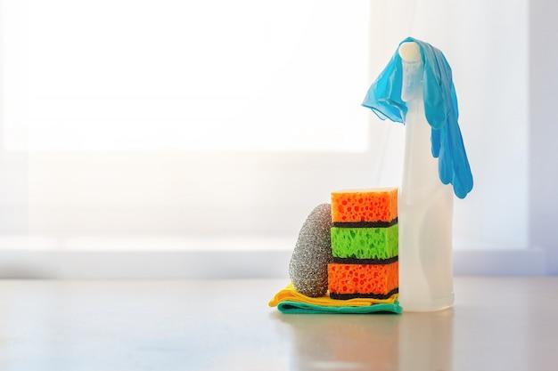 Nettoyant en aérosol de bouteille blanche et éponge propre sur une table.